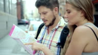 Young attractive couple with a city map trying to find a right direction. video