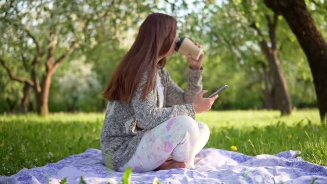 Young attractive girl clicks on the phone screen and drinks coffee in the park video