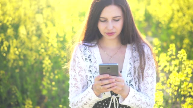 Young attractive girl clicks on the phone screen in a rape field video
