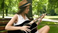 Young attractive girl learning how to play guitar in the park video