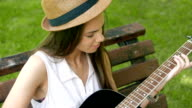 Young attractive girl learning how to play guitar outdoors video