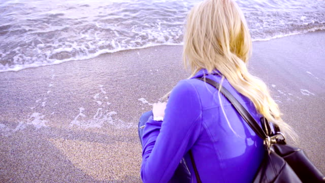 Young attractive girl sits by the sea and smiles video