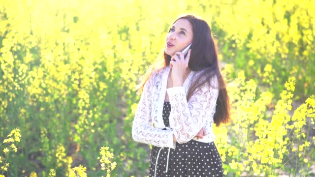 Young attractive girl talking on the phone in a rapeseed field video