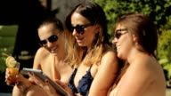Young attractive girls with tablet on vacation video