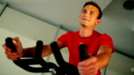 Young attractive man cycling on the exercise bike in the gym video