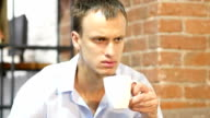 young attractive man drinking a coffee  in creative work space video