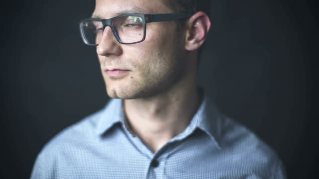 Young attractive man having a serious look isolated on black background. video