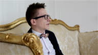 Young attractive man in glasses is sitting on a golden sofa and talking. video