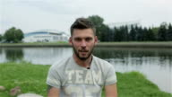 Young attractive man with a beard gives an interview on the banks of the river. video