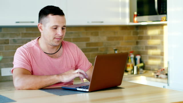 Young attractive man working with laptop at the kitchen video