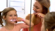 Young attractive mom and her cute daughter brush their teeth. Slow motion video