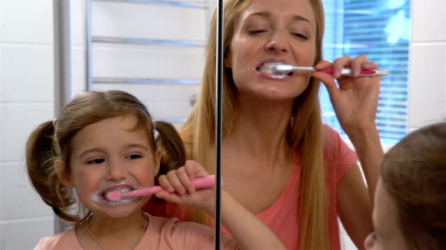 Young attractive mom and her cute daughter brush their teeth. video