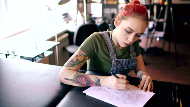 Young attractive red haired woman tattoo artist sitting at table and creating sketch for tattooing in studio indoors video