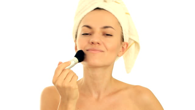 Young attractive woman applying blusher, isolated on white video