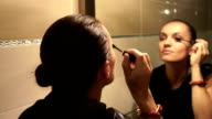 Young attractive woman applying mascara in front of the mirror video