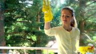 Young attractive woman cleaning a window with a special detergent spray and a brush and smiling at camera. Dolly shot. video