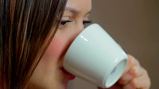 Young attractive woman drinks coffee smiles, pretty face make-up video