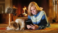 A young attractive woman enjoys the tablet. In a comfortable house on a background of fire. Next to it is a dog video