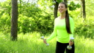 Young attractive woman exercising with dumbbells in the park video