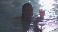 Young attractive woman gets out of the pool and drinks a cocktail in a spa wellness center. video