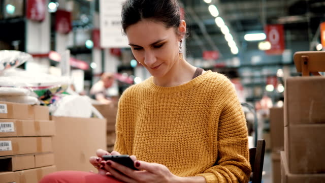 young attractive woman in the orange jacket uses a smartphone, sitting among the things in a store video