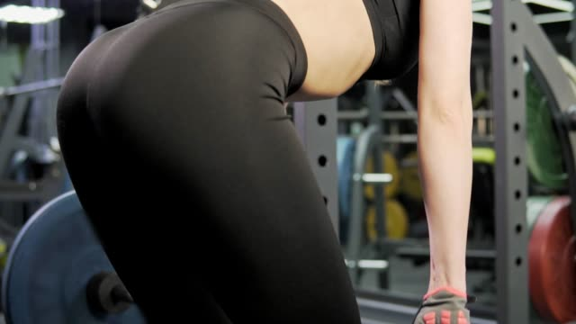 Young attractive woman is raising a bar in the gym video