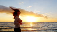 Young attractive woman jogging on the beach at sunset. Beautiful clouds and breathtaking sunset. Steadicam slow motion video. Hair fluttering in the wind video
