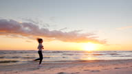 Young attractive woman jogging on the beach at sunset Full length. Beautiful clouds and breathtaking sunset. Steadicam slow motion video video