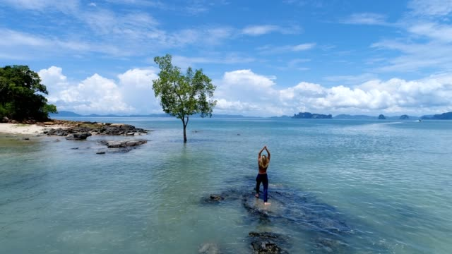Young attractive woman practicing exercise in tropical settings, drone shot video