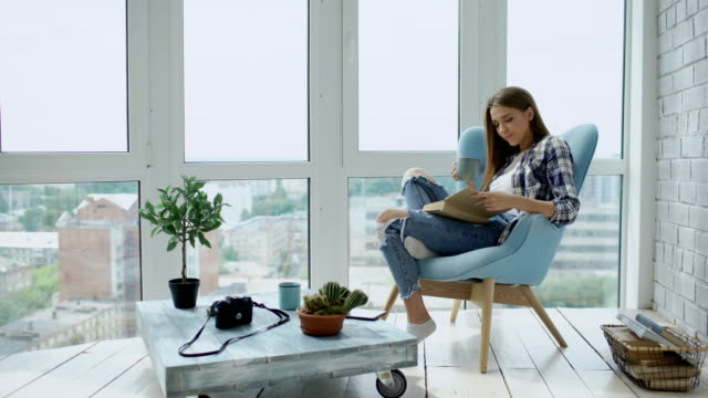 Young attractive woman read book and drink coffee sitting on balcony in modern loft apartment video