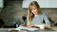 Young attractive woman reading a book in the kitchen. Nearby stands a glass of milk. Concept - healthy eating and a healthy lifestyle video