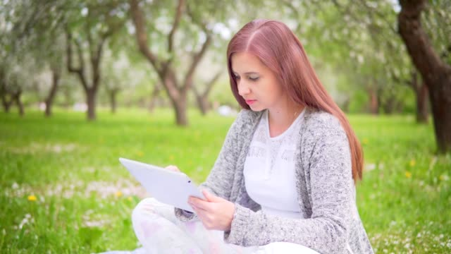 Young attractive woman typing text on tablet in park video