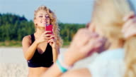 Young attractive woman with a smartphone pictures of his girlfriend on the beach video
