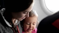 Young attractive woman with little daughter traveling at airplane. video
