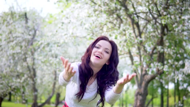 Young attractive woman with open arms in the park smiling video