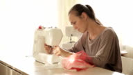 Young attractive woman working at sewing machine video