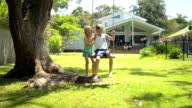 DOLLY: Young Australian kids swinging at the garden video