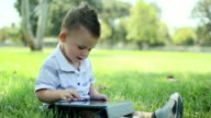 Young Baby Boy Using Tablet Touch Screen Outside At Park video