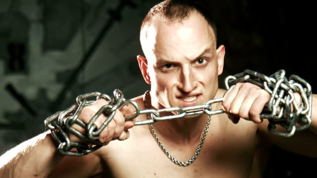 Young bald man trying to thorn the metal chain video
