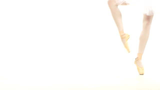 Young ballerina dancing, closeup on legs and shoes, standing in pointe position video
