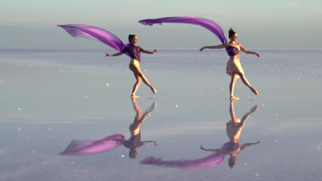 Young ballerinas dancing on the salt lake with color tulle video