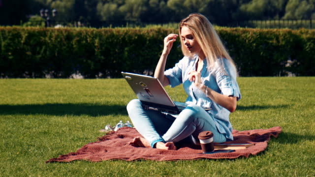 Young barefoot woman using a laptop outdoors video