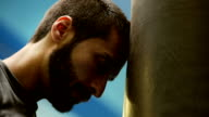 Young beard boxer resting on punching bag video HD video