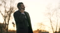Young bearded business man in coat talking at smartphone and making deals on street with sunlight backlit in evening time video