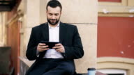 Young bearded businessman reading news on tablet computer and drink coffee during break near his office building video