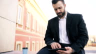 Young bearded businessman reading news on tablet computer during break in city street video