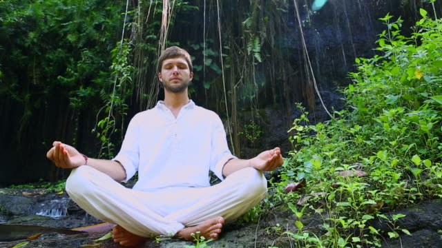 Young bearded man doing yoga meditation near waterfall video