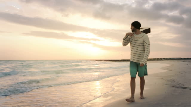 Young bearded man front view with guitar walk along beach sea-side at sunrise sunset in summer day - gimbal steadicam HD video footage video