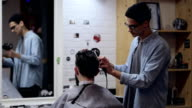 Young bearded man in barber shop. Barber combing hair with hairdryer. video