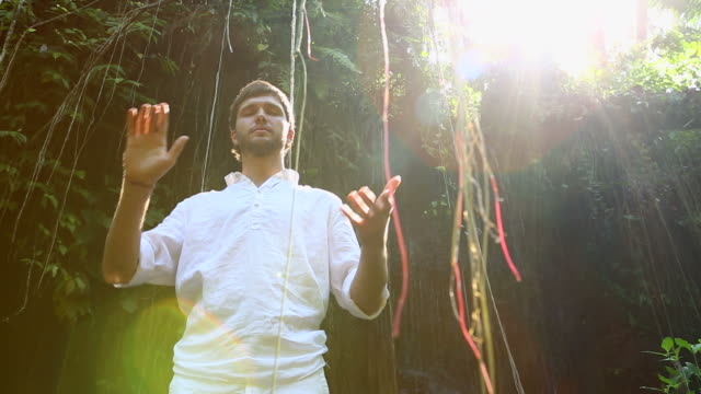 Young bearded man meditating in a jungle video